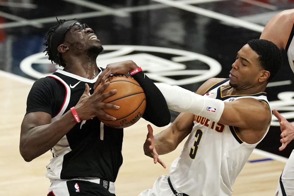 Los Angeles Clippers guard Reggie Jackson, left, has his shot blocked by Denver Nuggets guard Shaquille Harrison during the second half of an NBA basketball game Saturday, May 1, 2021, in Los Angeles. (AP Photo/Mark J. Terrill)
