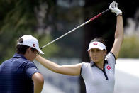 Albane Valenzuela, of Switzerland, stretches on the 11th fairway as her brother and caddy, Alexis Valenzuela, stands with her bag during a practice round prior to the women's golf event at the 2020 Summer Olympics, Monday, Aug. 2, 2021, at the Kasumigaseki Country Club in Kawagoe, Japan. (AP Photo/Matt York)
