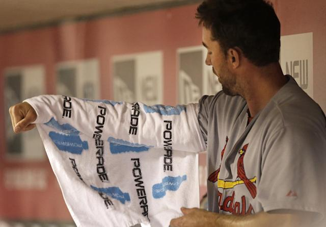 St. Louis Cardinals starting pitcher Adam Wainwright wraps his pitching arm in the fourth inning of a baseball game against the Cincinnati Reds, Sunday, May 25, 2014, in Cincinnati. (AP Photo/Al Behrman)