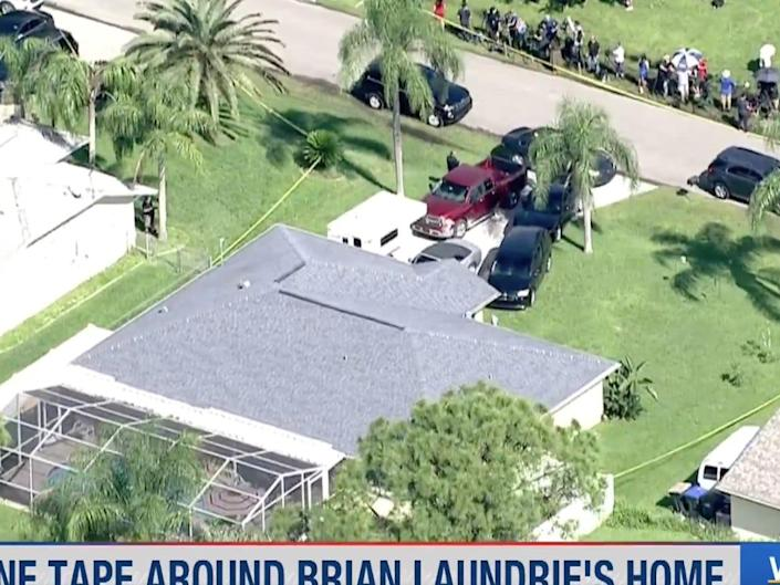 Police swarm the home of Brian Laundrie.
