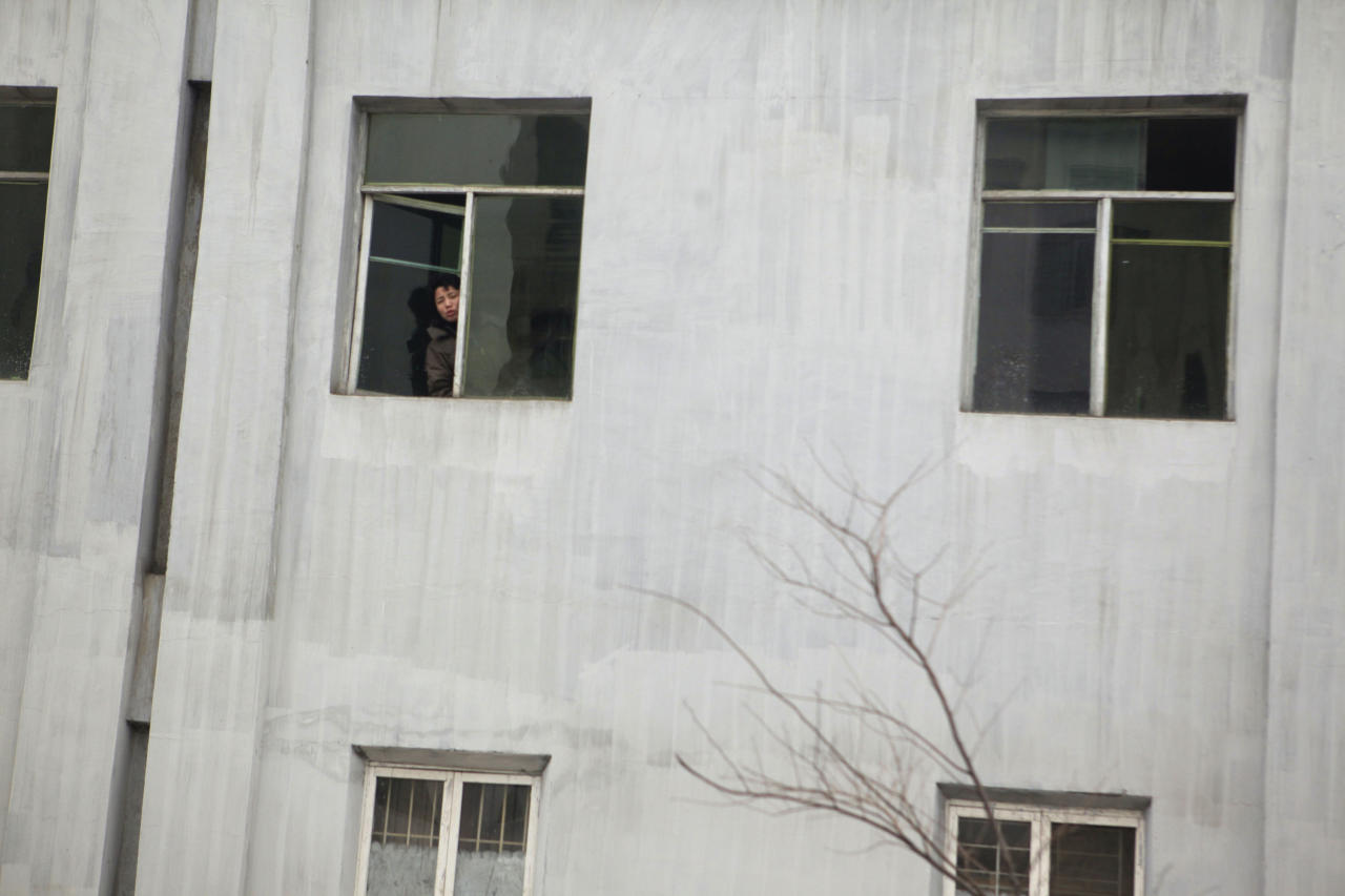 A North Korean woman peeps out of a window at a residential building in Pyongyang, North Korea, Thursday, April 12, 2012. (AP Photo/Ng Han Guan)