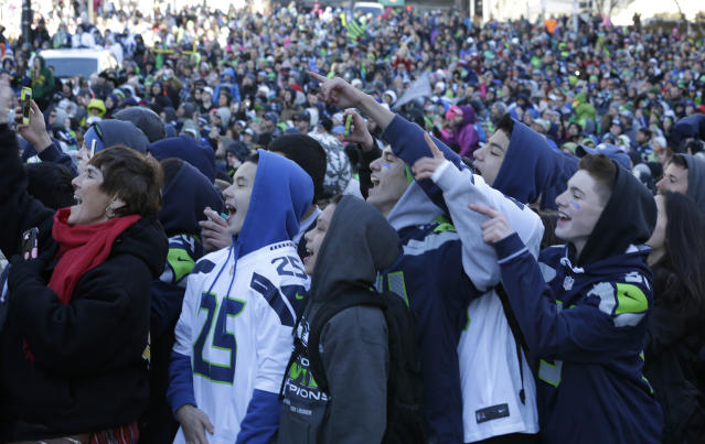 Seattle Seahawks fans watch during the Super Bowl champions parade on Wednesday, Feb. 5, 2014, in Seattle. The Seahawks beat the Denver Broncos 43-8 in NFL football's Super Bowl XLVIII on Sunday. (AP Photo/Elaine Thompson)