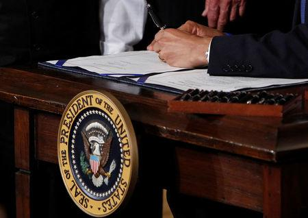 U.S. President Barack Obama signs the Affordable Care Act, dubbed Obamacare, the comprehensive healthcare reform legislation during a ceremony in the East Room of the White House in Washington, U.S., March 23, 2010. REUTERS/Jim Young/File Photo