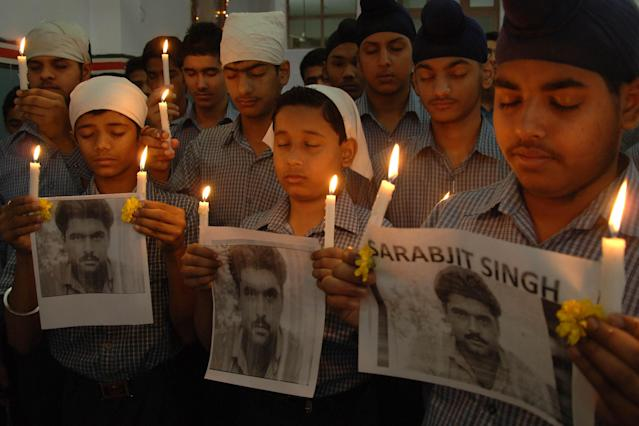 Indian students pose with lighted candles as they pay tribute to the late Sarabjit Singh at a school in Amritsar on May 2, 2013. An Indian man on death row in Pakistan for spying died nearly a week after he was attacked by fellow prisoners, who were swiftly charged with murder as New Delhi demanded justice. Sarabjit Singh, who was sentenced 16 years ago over deadly bombings, died in the early hours as a result of the savage assault in Lahore's Kot Lakhpat jail, a senior doctor at Jinnah hospital in the eastern city told AFP. AFP PHOTO/NARINDER NANU (Photo credit should read NARINDER NANU/AFP/Getty Images)