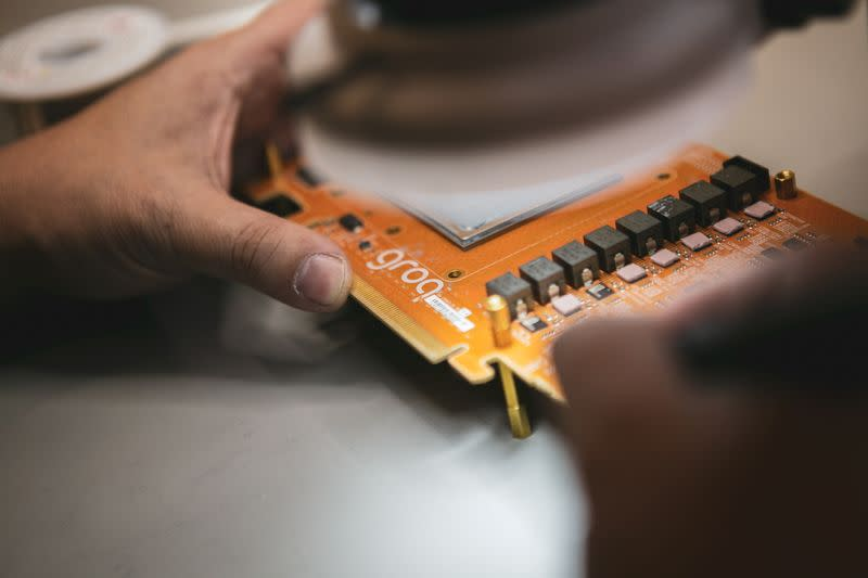 Engineer of Groq, a Silicon Valley AI chip design startup, works on a GroqCard, in this undated handout image