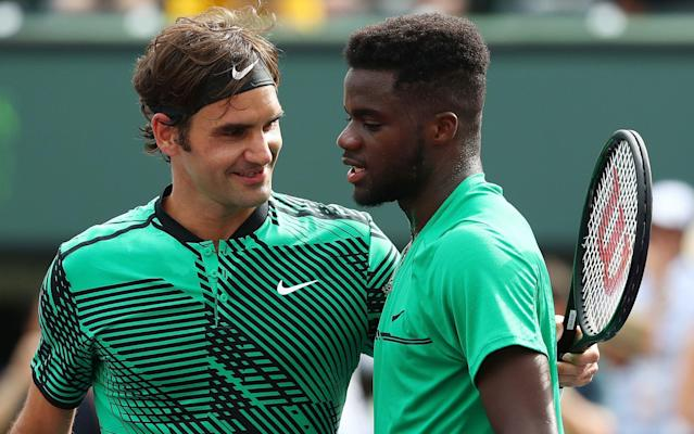 Roger Federer consoles Frances Tiafoe at the net - Getty Images North America