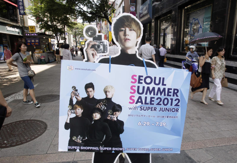 A cutout of South Korean K-pop boy group Super Junior is displayed to promote summer discount sale on a street in Seoul, South Korea, Thursday, July 26, 2012. South Korea's economic growth fell to a two-year low in the second quarter as exports and capital expenditures shrank due to a slowdown in its largest trading partner, China, and debt-crippled Europe.(AP Photo/Ahn Young-joon)