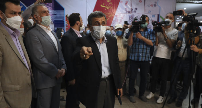 Former Iranian President Mahmoud Ahmadinejad, center, speaks with journalists while registering his name as a candidate for the June 18 presidential elections at the elections headquarters of the Interior Ministry in Tehran, Iran, Wednesday, May 12, 2021. The country's former firebrand president will run again for office in upcoming elections in June. The Holocaust-denying Ahmadinejad has previously been banned from running for the presidency by Supreme Leader Ayatollah Ali Khamenei in 2017, although then, he registered anyway. (AP Photo/Vahid Salemi)