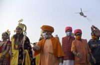 Uttar Pradesh state Chief Minister Yogi Adityanath, center, receives artists dressed as Hindu god Ram, goddess Sita and Lakshman as they alight from a helicopter on the banks of river Saryu on the eve of Diwali, the Hindu festival of lights, in Ayodhya, India, Friday, Nov. 13, 2020. Diwali will be celebrated on Saturday. (AP Photo/Rajeev Bhatt)