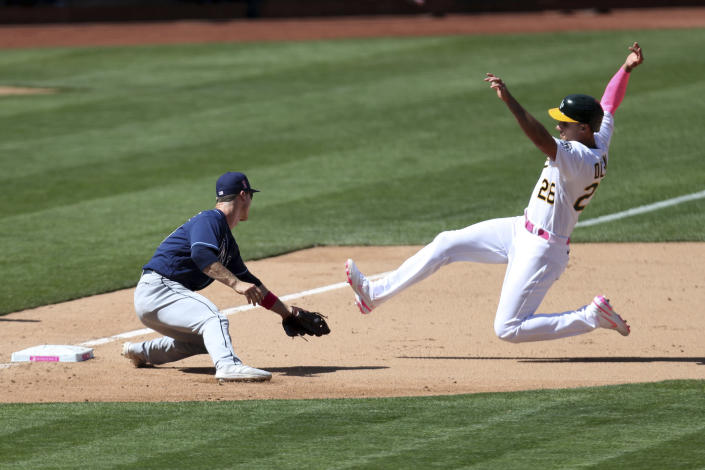 CORRECTS TO TAGGED OUT ON A PASSED BALL NOT A STEAL-ATTEMPT - Oakland Athletics' Matt Olson, right, is tagged out on a passed ball by Tampa Bay Rays' Joey Wendle during the eighth inning of a baseball game in Oakland, Calif., Sunday, May 9, 2021. (AP Photo/Jed Jacobsohn)