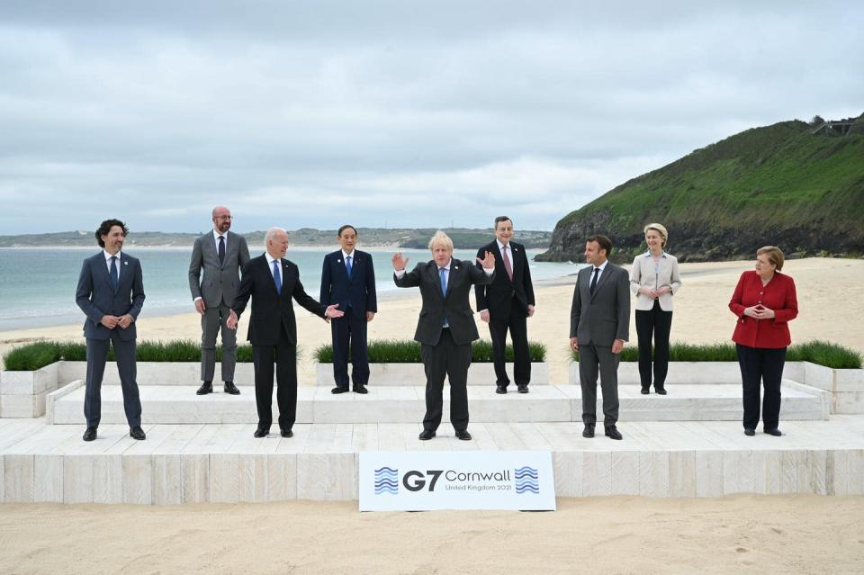 Boris Johnson stands with his arms raised in front of other G7 leaders on a beach.