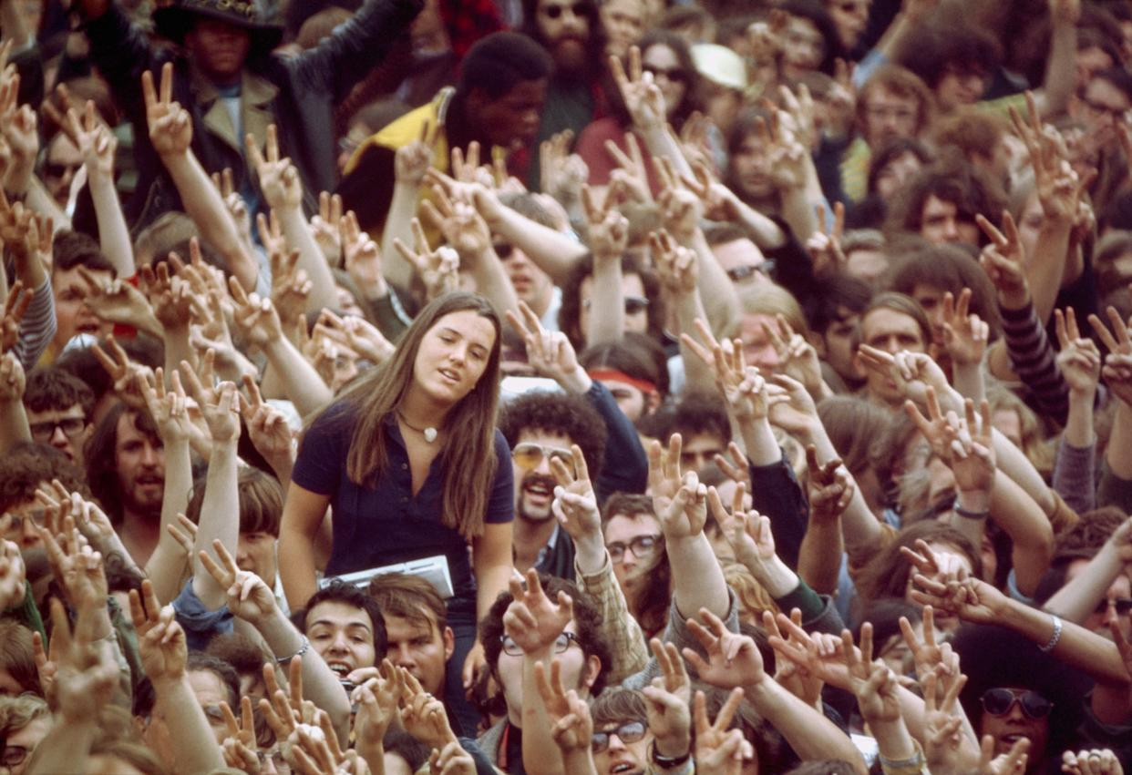 A woman emerges from a crowd of peace demonstrators making peace signs and singing for peace at a demonstration against the Vietnamese War circa 1969.