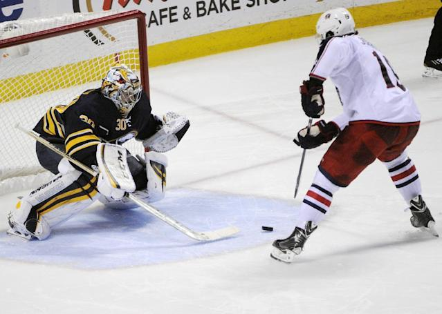 Buffalo Sabres goaltender Ryan Miller (30) tries to knock the puck from Columbus Blue Jackets center Ryan Johansen, right, as he scores the game-winning goal during the team shootout in an NHL hockey game in Buffalo, N.Y., Saturday, Jan.18, 2014. Columbus won 4-3. (AP Photo/Gary Wiepert)