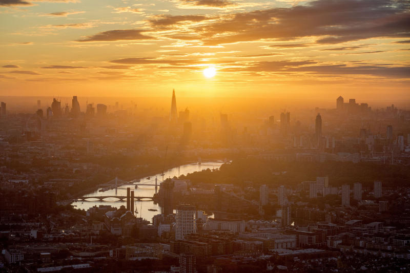The sun rises over London, looking east with tall building at centre The Shard, and bridges from nearest, Battersea Bridge, Albert Bridge and Chelsea Bridge across the River Thames, shrouded in mist as warmer weather returns to the south of England, Sunday Aug. 13, 2017. Recent periods of rain and cold weather seems to have moved from the region. (Victoria Jones/PA via AP)