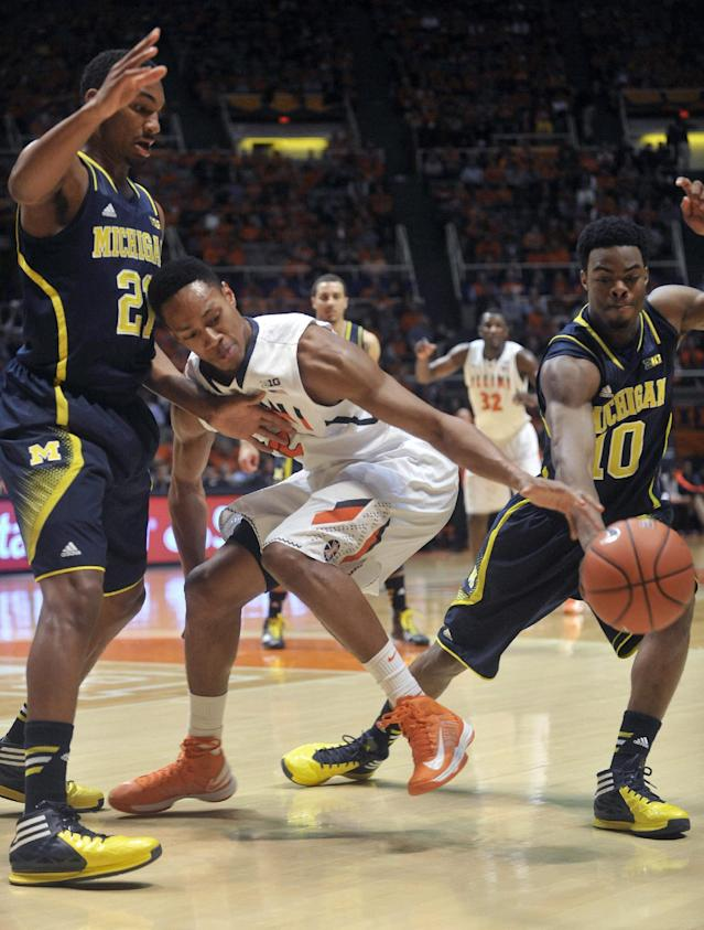 Illinois guard Joseph Bertrand (2) loses the ball between Michigan guards Zak Irvin (21) and Derrick Walton Jr. (10) during the first half of an NCAA college basketball game Tuesday, March 4, 2014, in Champaign, Ill. (AP Photo/Rick Danzl)