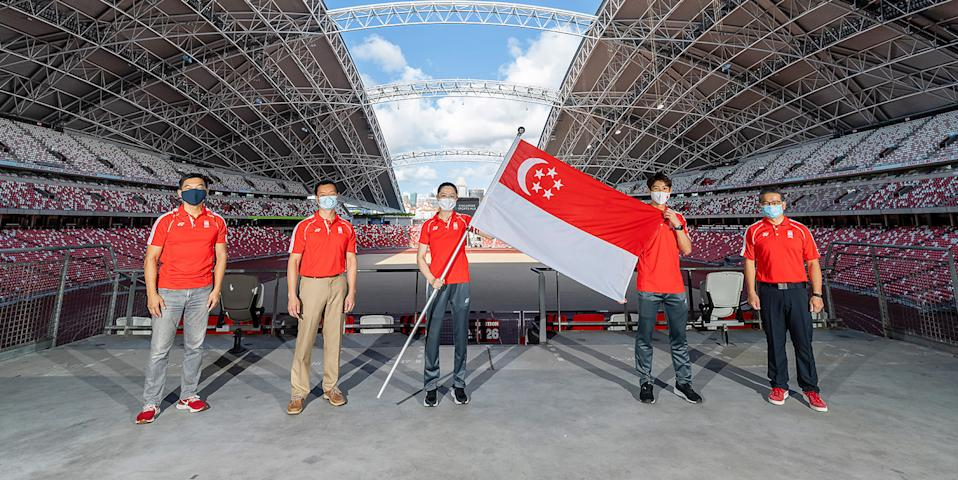 Team Singapore flag bearers Yu Mengyu (third from left) and Loh Kean Yew (second from right) receiving the Singapore flag at the National Stadium. With them are (from left) SNOC president Tan Chuan-Jin, Team Singapore chef de mission Dr Benedict Tan, and Minister for Community, Culture and Youth Edwin Tong. (PHOTO: Singapore National Olympic Council)
