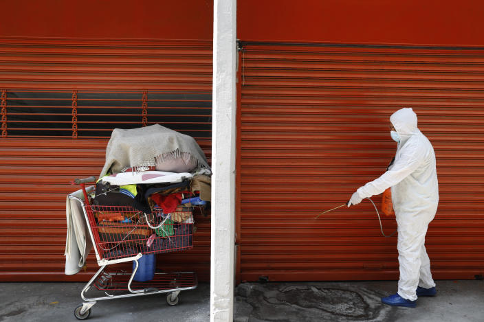 Edwin Monroy, 23, an employee of the capital's Ministry of Inclusion and Social Wellbeing, SIBISO, sprays a disinfectant solution on the ground in an area where homeless men and women often sleep during the night, outside the Basilica of Our Lady of Guadalupe in Mexico City, Wednesday, April 8, 2020. To combat the spread of the novel coronavirus, SIBISO has ramped up the activity of their mobile health clinic catering to the homeless and has begun disinfecting areas where many sleep. (AP Photo/Rebecca Blackwell)
