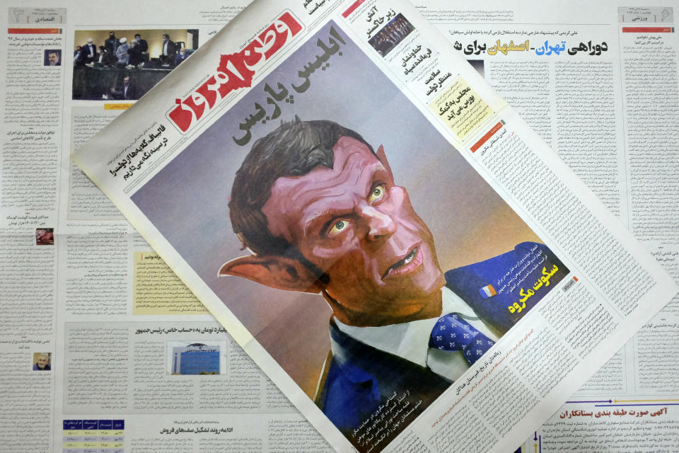 The front page of the Tuesday, Oct. 27, 2020 edition of the Iranian hard-line Iranian newspaper, Vatan-e Emrooz, depicts French President Macron as the devil and called him Satan in a cartoon. Iran summoned a French diplomat to protest Macron's staunch support of secular laws that deem caricatures depicting the Prophet Muhammad as protected under freedom of speech. (AP Photo/Vahid Salemi)