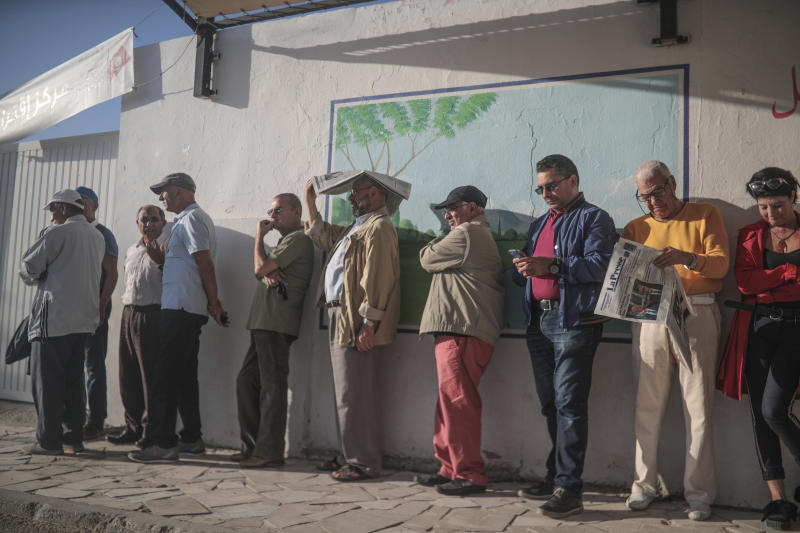 People queue outside a polling station during the second round of the presidential election, in Tunis, Tunisia, Sunday, Oct. 13, 2019. Tunisians are voting for president, choosing between a law professor and populist tycoon. (AP Photo/Mosa'ab Elshamy)