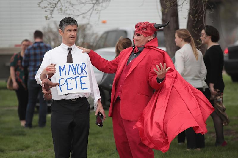 Three protesters dressed as the devil, Jesus and Buttigieg came to demonstrate in front of a house where the mayor was meeting with voters (AFP Photo/SCOTT OLSON)