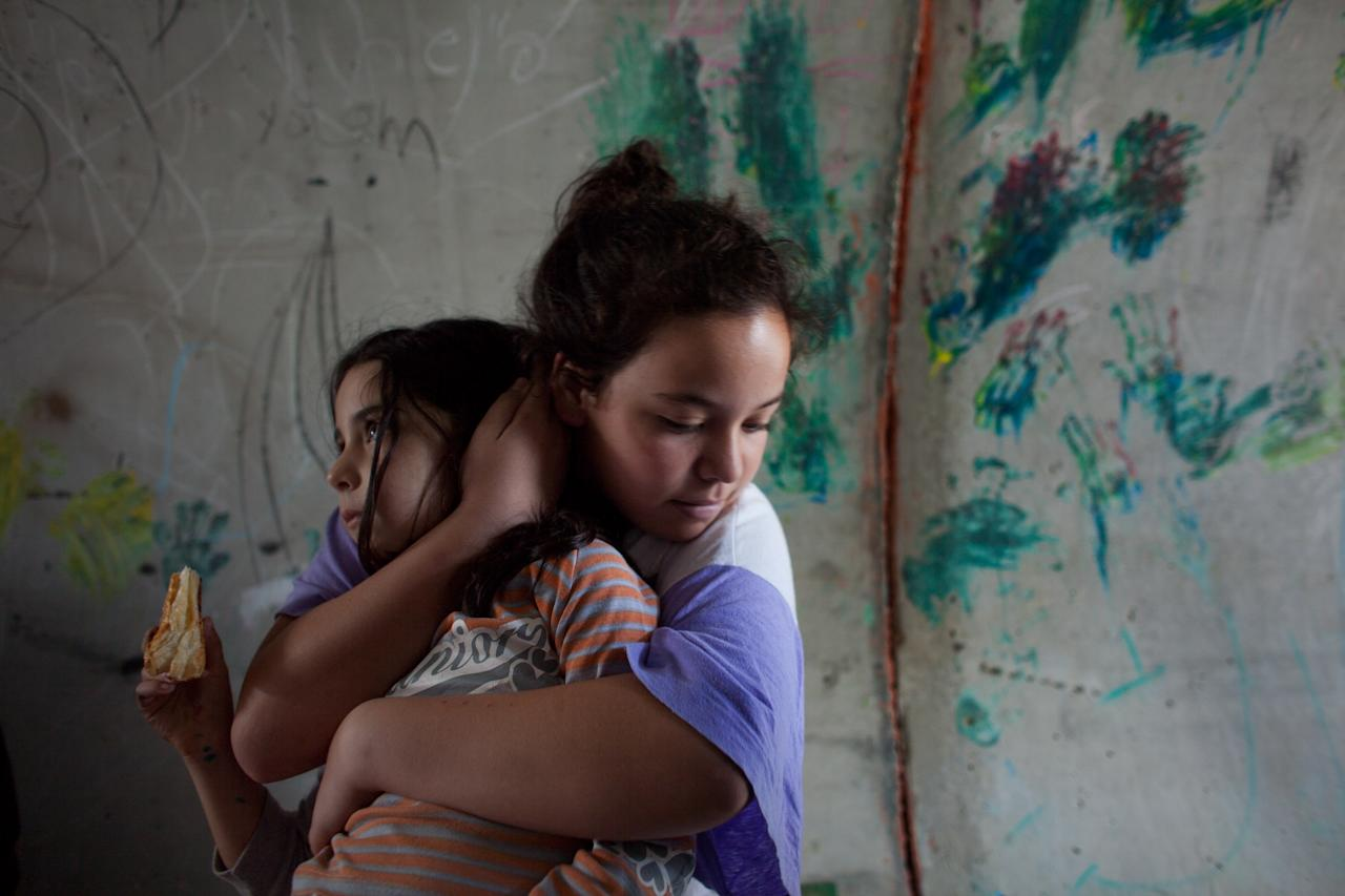 NITZAN, ISRAEL - NOVEMBER 19:  (ISRAEL OUT)  An Israeli girl holds her sister as they take cover in a large concrete pipe used as a bomb shelter during a rocket attack from the Gaza Strip on November 19, 2012 in Nitzan, Israel. According to reports November 19, 2012, at least 90 Palestinians have been killed and more than 700 wounded during the Israeli offensive in the Gaza Strip.  (Photo by Uriel Sinai/Getty Images)