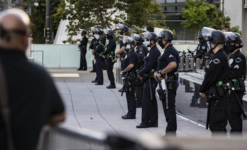 LOS ANGELES, CA - MAY 28, 2020: Los Angeles Police officers in riot gear and face masks stand on the other side of metal fence barriers in front of headquarters to keep Black Lives Matter protesters from advancing in a rally to protest the death of George Floyd during the coronavirus pandemic on May 28, 2020 in Los Angeles, California. (Gina Ferazzi / Los Angeles Times)