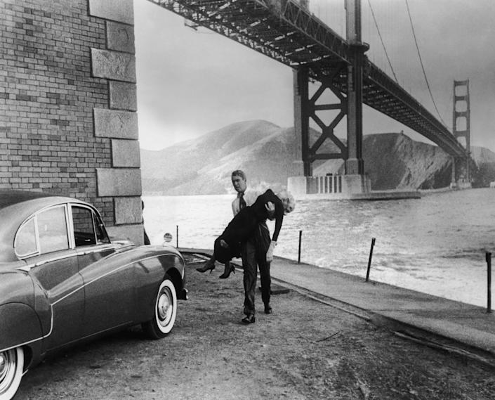 "Jimmy Stewart carries an inert Kim Novak to a Rolls-Royce beneath the Golden Gate Bridge in ""Vertigo."""