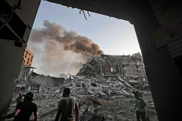 PHOTO: People gather in front of the rubble of the Al-Sharouk tower that collapsed after being hit by an Israeli air strike, in Gaza City, May 12, 2021. (Mohammed Abed/AFP via Getty Images)