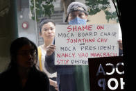 """Protestors are seen looking into the Chinatown Museum Reopens during the press preview of """"Responses: Asian American Voices Resisting the Tides of Racism"""", Wednesday, July 14, 2021, in New York. (AP Photo/Mary Altaffer)"""