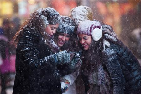 Tourists look at a camera to see photographs they took of themselves in a snowstorm in Times Square, Midtown, New York January 3, 2014. REUTERS/Darren Ornitz