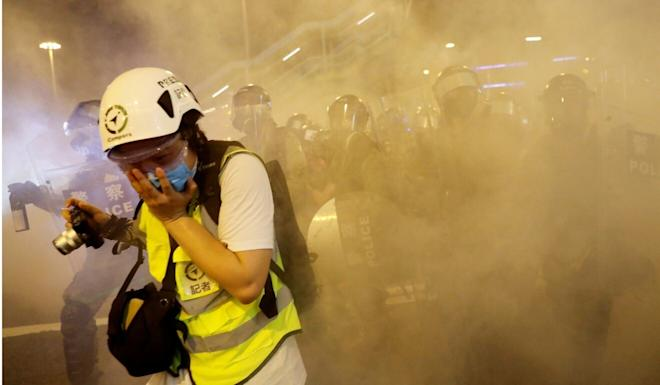 A journalist covers her face after police fire tear gas during a protest in August last year. Photo: Reuters