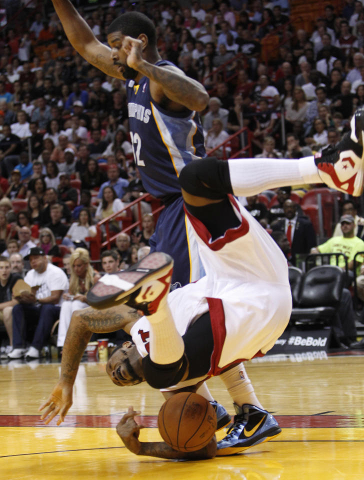 Miami Heat forward Udonis Haslem, foreground, is upended as he goes up for a shot against Memphis Grizzlies guard O.J. Mayo during the first half of an NBA basketball game, Friday, April 6, 2012 in Miami. (AP Photo/Wilfredo Lee)