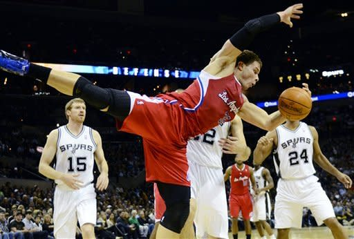 Los Angeles Clippers forward Blake Griffin tries to control a rebound in front of San Antonio Spurs' Matt Bonner (15), Tiago Splitter, of Brazil, (22) and Richard Jefferson (24) during the first half of an NBA basketball game in San Antonio, Wednesday, Dec. 28, 2011. (AP Photo/Bahram Mark Sobhani)