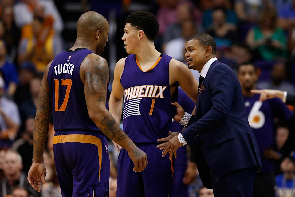 Interim head coach Earl Watson of the Phoenix Suns talks with P.J. Tucker #17 and Devin Booker #1 during the second half of the NBA game against the Golden State Warriors at Talking Stick Resort Arena on February 10, 2016 in Phoenix, Arizona.  The Warriors defeated the Suns 112-104. NOTE TO USER: User expressly acknowledges and agrees that, by downloading and or using this photograph, User is consenting to the terms and conditions of the Getty Images License Agreement.  (Photo by Christian Petersen/Getty Images)