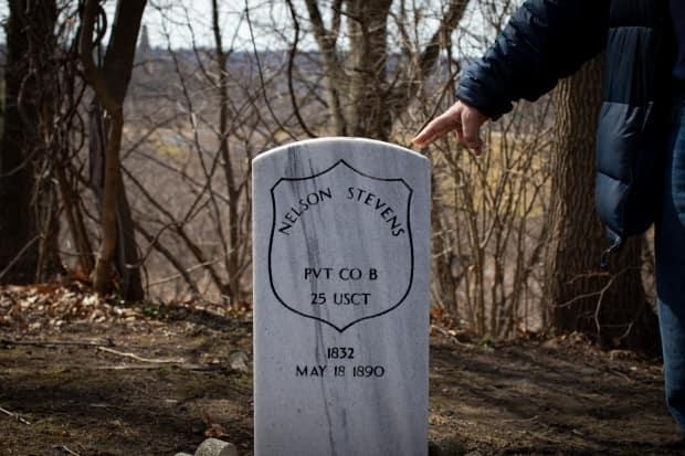 Historian Robin McKee points to the Hamilton Cemetery burial site of Nelson Stevens, a Black veteran of the Civil War. (Evan Mitsui/CBC - image credit)