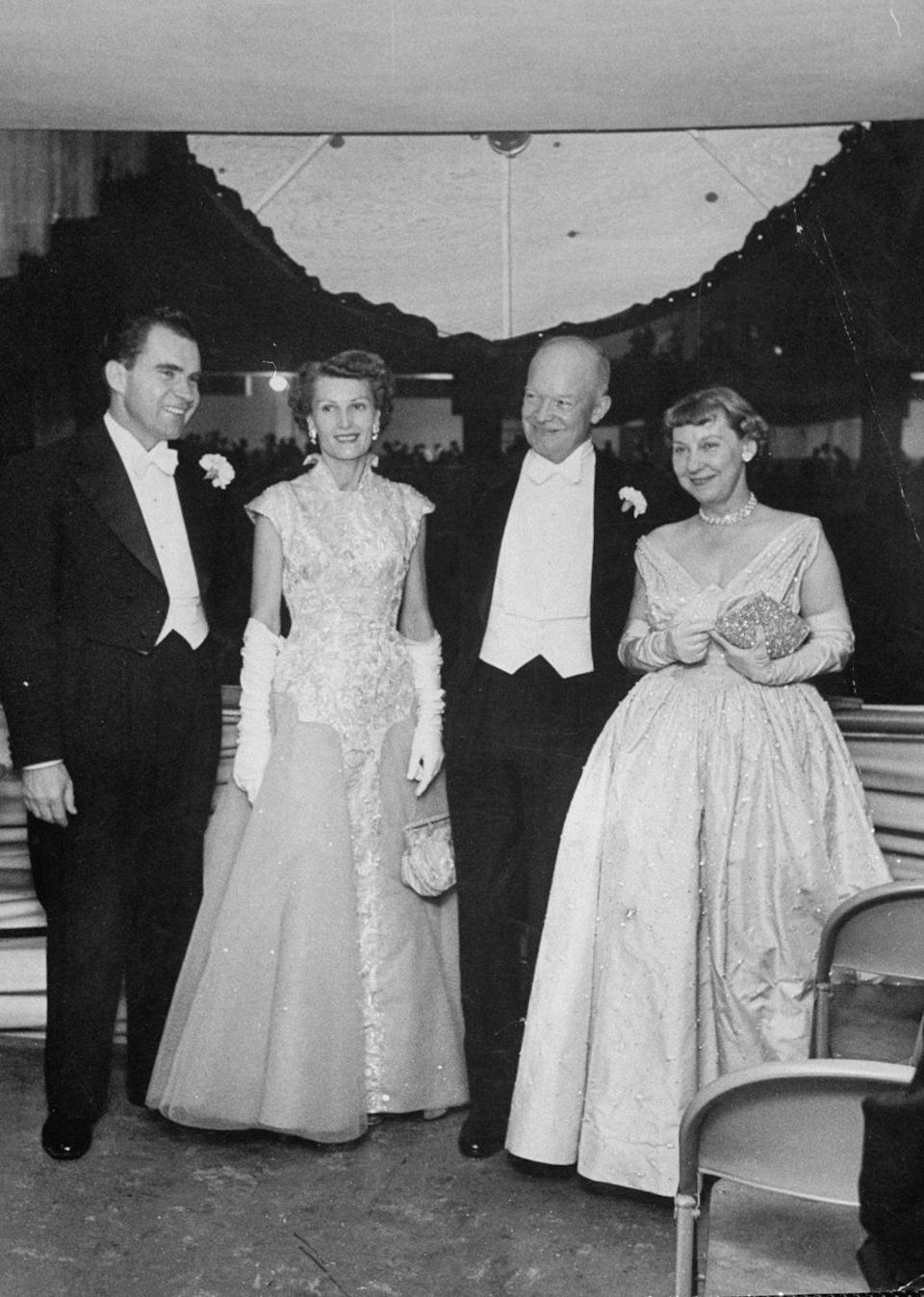 """<p>At his first inauguration in 1953, Dwight Eisenhower is joined by his wife, Mamie Eisenhower, Vice President Nixon, and his wife, Patricia Nixon. There were <a href=""""https://www.eisenhowerlibrary.gov/sites/default/files/research/online-documents/inauguration-1957/inaugural-ball-program.pdf"""" rel=""""nofollow noopener"""" target=""""_blank"""" data-ylk=""""slk:two inaugural balls held in honor of Eisenhower"""" class=""""link rapid-noclick-resp"""">two inaugural balls held in honor of Eisenhower</a> that evening, one in the Armory and the other in the McDonough Gymnasium at Georgetown University. </p>"""