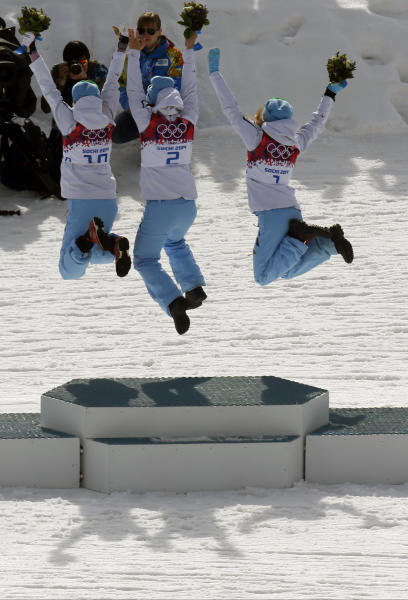 From left, bronze medalist Norway's Kristin Stoermer Steira, gold medalist Norway's Marit Bjoergen and silver medalist Norway's Therese Johaug jump in celebration during the flowers ceremony for the women's 30K cross-country race at the 2014 Winter Olympics, Saturday, Feb. 22, 2014, in Krasnaya Polyana, Russia. (AP Photo/Dmitry Lovetsky)