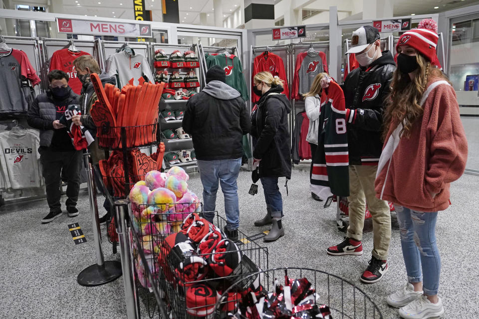 Fans line cup to pay for their purchases at a New Jersey Devils team store before an NHL game between the Devils and the New York Islanders, Tuesday, March 2, 2021, in Newark, N.J. It was the first time fans were allowed in the Prudential Center under New Jersey's more relaxed COVID-19 rules. (AP Photo/Kathy Willens)