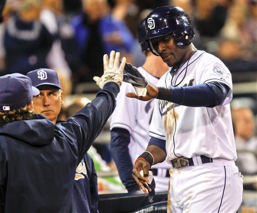 San Diego Padres' Orlando Hudson high fives at the dugout after scoring the tie run against the Arizona Diamondbacks in the seventh inning of a baseball game Tuesday, April 10, 2012 in San Diego. (AP Photo/Lenny Ignelzi)