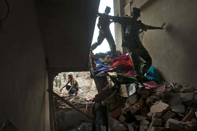 Bangladeshi soldiers walk amid the rubble of the garment factory building that collapsed on April 24 as they continue search operation in Savar, near Dhaka, Bangladesh, Sunday, May 12, 2013. Search teams resumed their rain-interrupted work Sunday as the death toll from the collapse continued to climb past 1,100. (AP Photo/Ismail Ferdous)