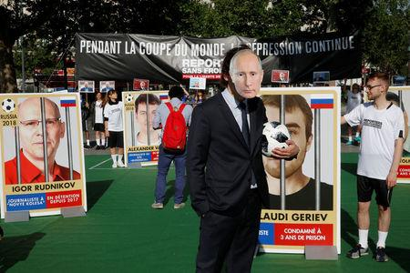 A Reporter Without Borders (RSF) activist, wearing a mask depicting Russian President Vladimir Putin, stands next to giant portraits of seven imprisoned Russian journalists on place de la Republique, transformed into a soccer field to denounce abuse of press freedom in Russia as the World Cup is about to kick off, in Paris, France, June 13, 2018.  REUTERS/Philippe Wojazer