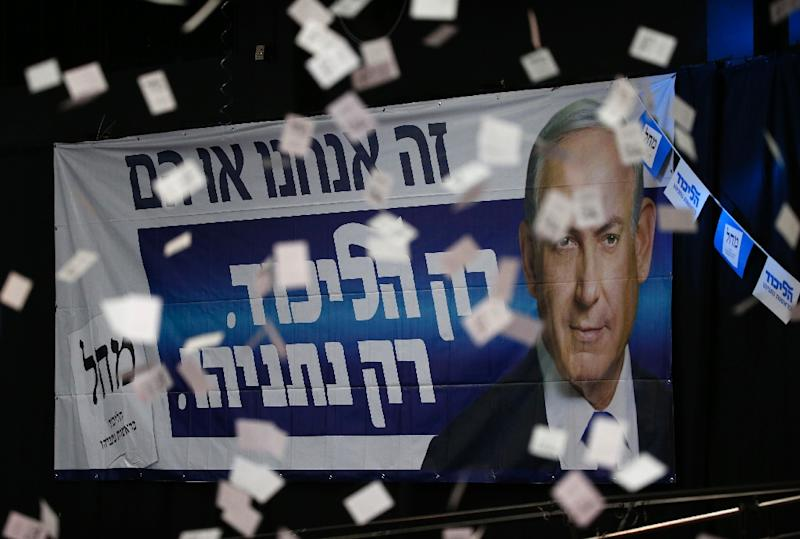 Confetti falls in front of a poster of Israeli Prime Minister Benjamin Netanyahu as supporters of his Likud party wait for election results (AFP Photo/Jack Guez)