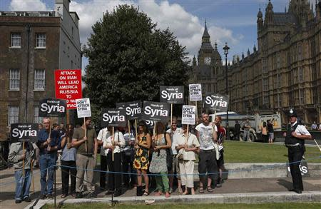Demonstrators hold placards outside the Houses of Parliament in London