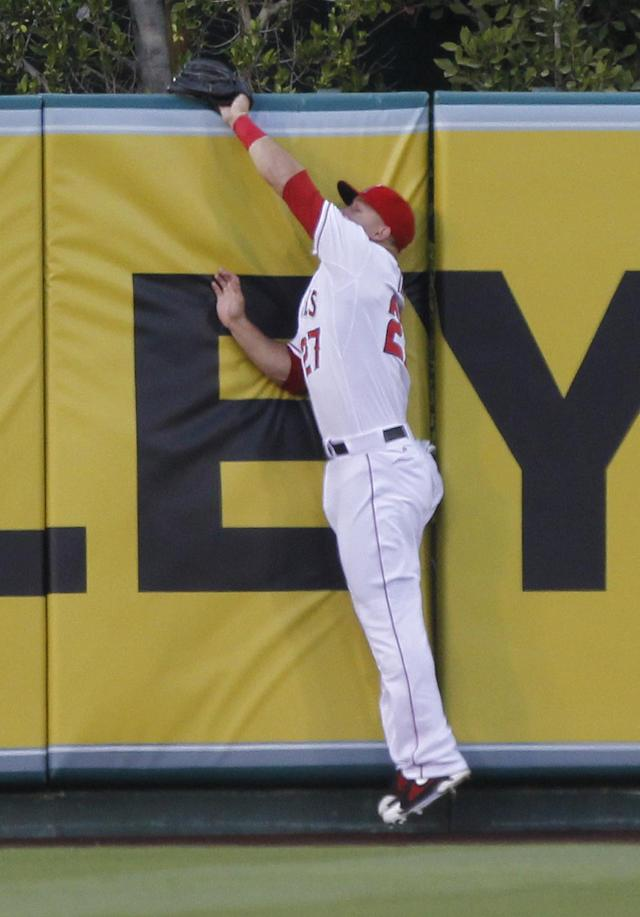 Los Angeles Angels center fielder Mike Trout jumps to catch a fly ball at the wall hit by Cleveland Indians' Lonnie Chisenhall in the first inning of a baseball game Tuesday, April 29, 2014, in Anaheim, Calif. (AP Photo/Alex Gallardo)