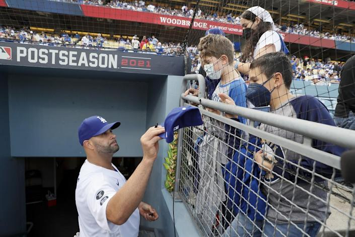 Los Angeles Dodgers' Albert Pujols signs autographs for fans before the game against the St. Louis Cardinals