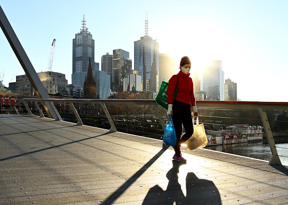 A woman wearing a face mask and carrying shopping bags walks across a bridge in Melbourne.