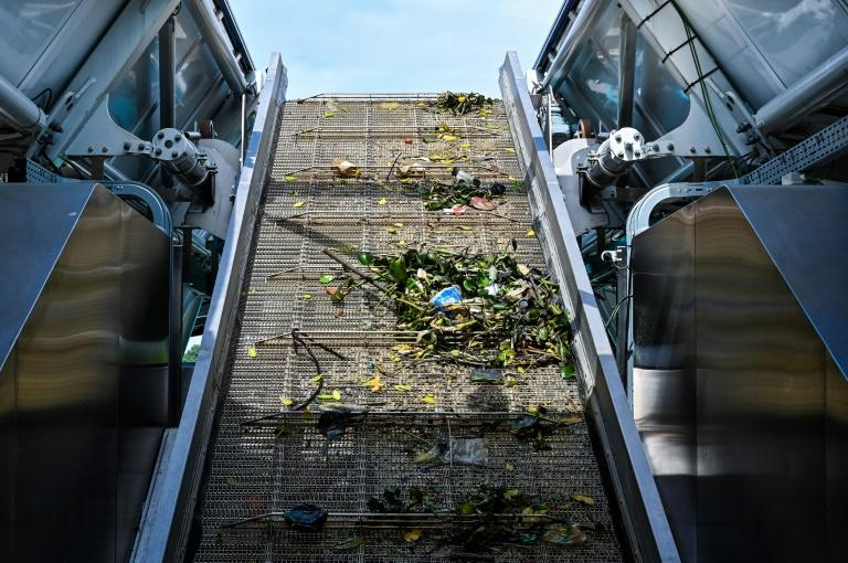 Trash collected by the Interceptor barge rolls up a conveyor belt before being dropped into dumpsters (AFP Photo/Mohd RASFAN)