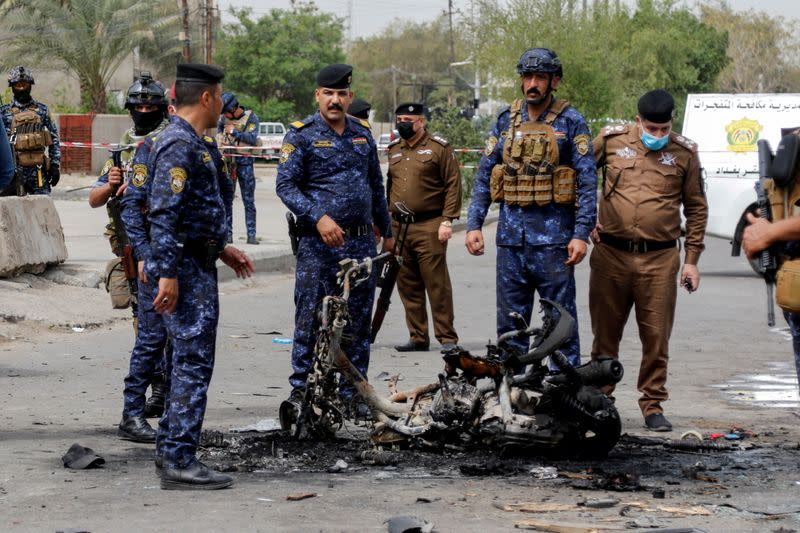 FILE PHOTO: Members of security forces inspect the scene of an explosion in Baghdad, Iraq March 23, 2021
