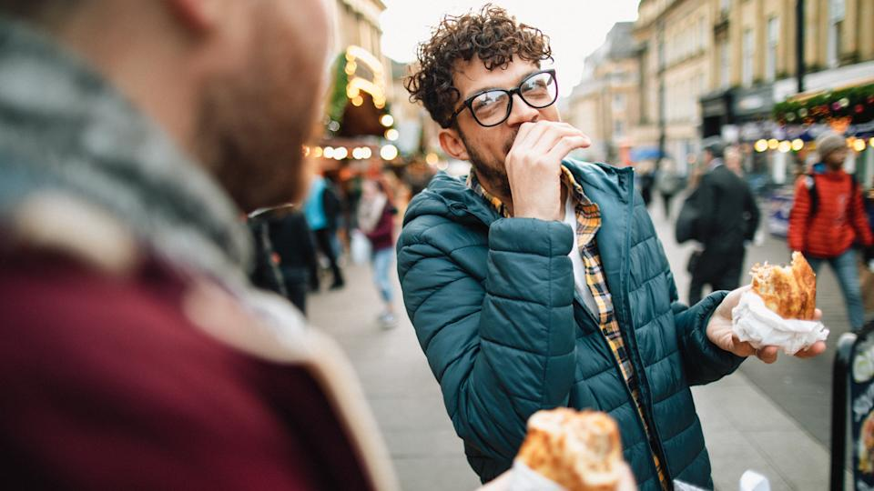 Two young gay men are eating hot food at a Christmas market.