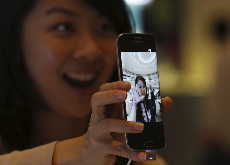 Woman uses the camera on a Samsung Galaxy S6 phone during a pre-launch event in Singapore